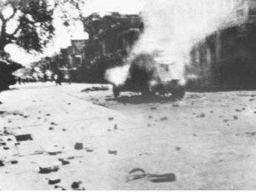 Archive photos: A military vehicle burns in the empty streets. | Image source - INP; courtesy - tribune.com.pk | Click for image.