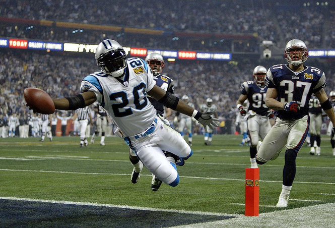 Even with billions in American Football, the game has not crossed America's borders. Here is Running back DeShaun Foster (20) of the Carolina Panthers scores on a 33 yard touchdown run against the New England Patriots during Super Bowl XXXVIII at Reliant Stadium on February 1, 2004 in Houston, Texas.  |  Getty Images File Photo
